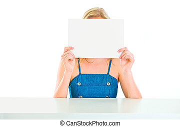 Girl sitting at table and holding blank paper in front of face