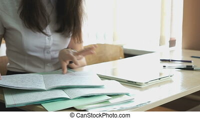 Girl sitting at the desk looks for the copybook - The girl...