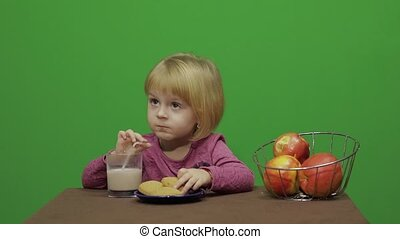 Girl sitting at the table and eating chocolate, cookies and drinks cacao