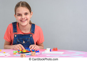 Girl sitting at the table playing board games, free space on the right