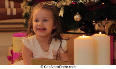 Girl Sitting by the Christmas Tree with Present Box