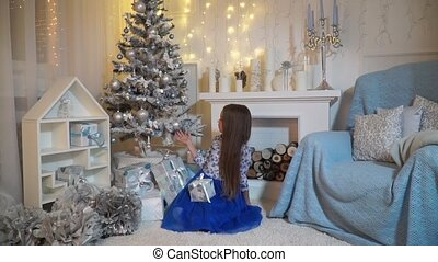 Girl sitting by the fireplace and playing with toy on the Christmas tree
