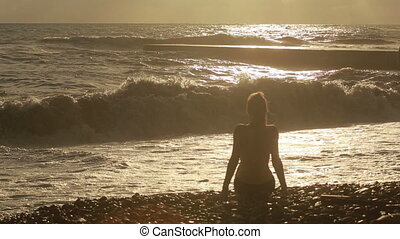 girl sitting by the sea. big waves. silhouette figures