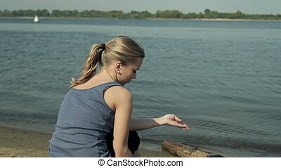 girl sitting by the water and looking into the distance HD