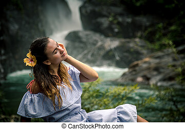 Girl sitting by the waterfall