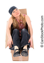 Girl sitting in a cardboard box, looking up