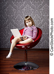 Girl sitting in a chair with a laptop