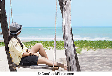 girl sitting in a wooden swing on the beach.