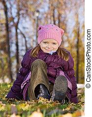 girl sitting in autumn park