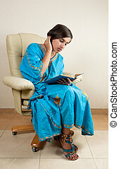 Girl sitting in chair reading book