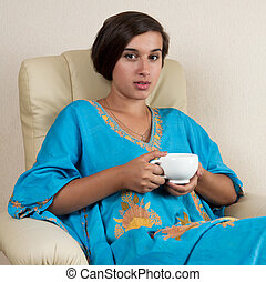 girl sitting in chair with cup