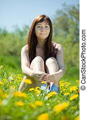 girl sitting in dandelion meadow