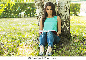 Girl sitting in grass, reading book in summer sun light