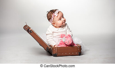 Girl sitting in suitcase with pink teddy bear