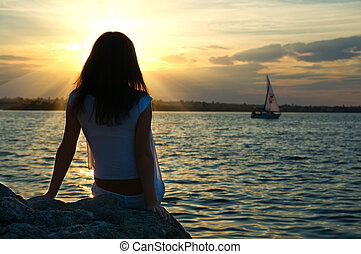 girl sitting in sunrays near water
