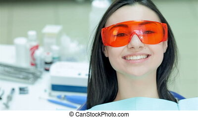 Girl sitting in the dental chair in red protective glasses -...