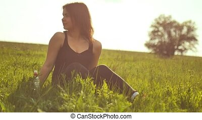 girl sitting in the grass after sports slow-motion video