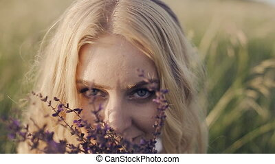 girl sitting in the grass and smelling a flower