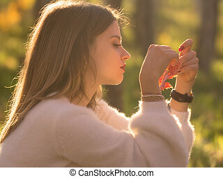 Girl sitting in the nature with a fallen leaf in her hand