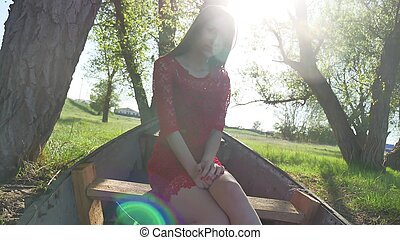 girl sitting in the old boat. lifestyle young woman in a red dress sitting on a old boat on the river in the summer