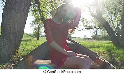 girl sitting in the old boat. young woman in a red dress sitting on a old boat on the river in the summer lifestyle