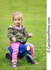 Girl sitting in the park on a motorbike