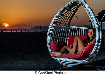 Girl sitting in the swing on the beach in the sunset