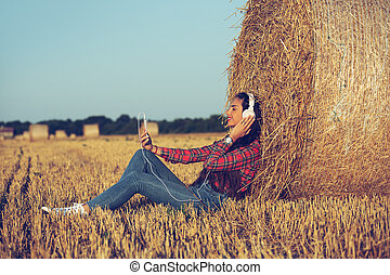 Girl sitting in the wheat field, listening music.