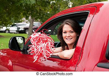 Girl Sitting in Truck with Pom Pom