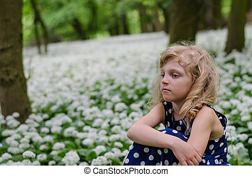 girl sitting in white meadow