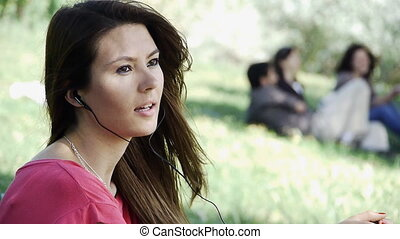 Girl sitting listening outdoor gras - Girl sitting at park....