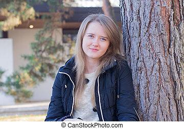 girl sitting near a tree