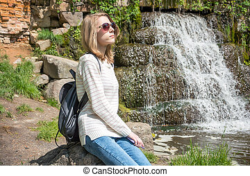 Girl sitting near a waterfall in a park
