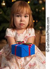 Girl sitting near Christmas tree with gift box