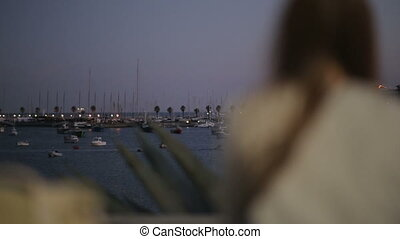 Girl sitting on a bench at embankment of ocean marina with boats in the evening and looking in a distance, boy come and seat near
