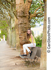 Girl sitting on a bench in park