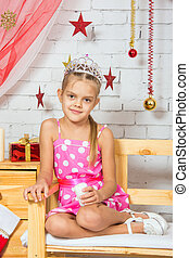Girl sitting on a bench in the Christmas room decoration