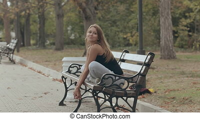 Girl sitting on a bench in the lotus position and resting