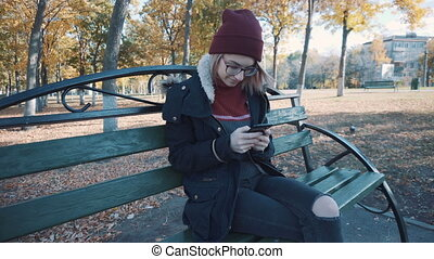 Girl sitting on a bench in the park with your phone. Girl in a jacket and hat