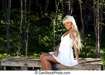girl sitting on a bench in the woods