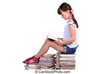 Girl sitting on a big pile of books and reading