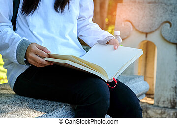 Girl sitting on a chair reading a book.