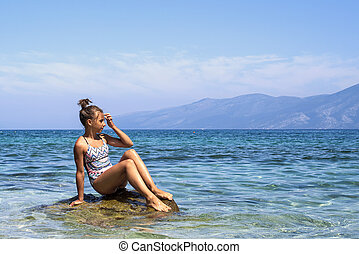 Girl sitting on a cliff face over the sea. Girl tourist sits on a mountain stone. Young brunette girl enjoying vacation. woman relaxing on coast admiring beautiful seascape.