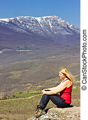 girl sitting on a cliff in the mountains