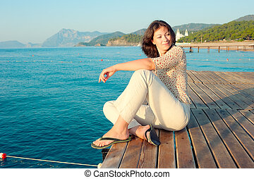 girl sitting on a pier near the sea and looking to the side