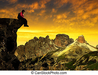 Girl sitting on a rock at sunset