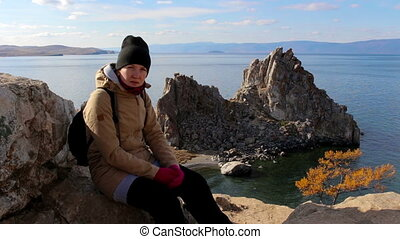 Girl sitting on a rock by the sea on a background of amazing landscape. Portrait