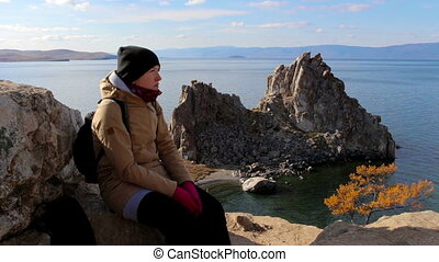 Girl sitting on a rock by the sea on a background of amazing landscape.