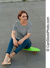 Girl sitting on a skateboard in the street.