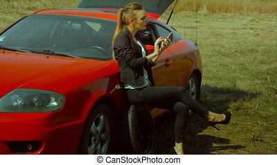 girl sitting on a spare wheel near the car and talking phone...